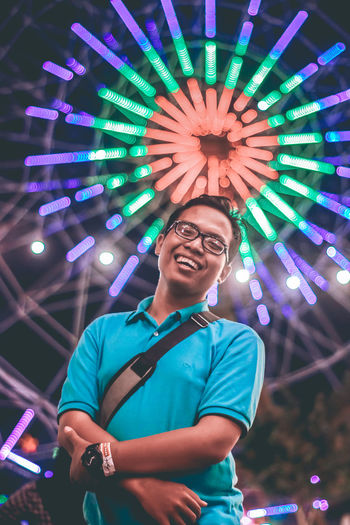 Portrait of smiling young man against illuminated ferris wheel