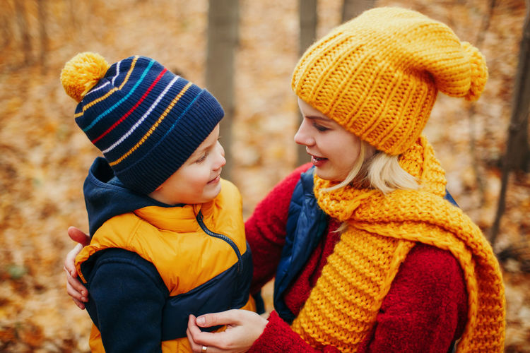 Woman with son at forest during autumn