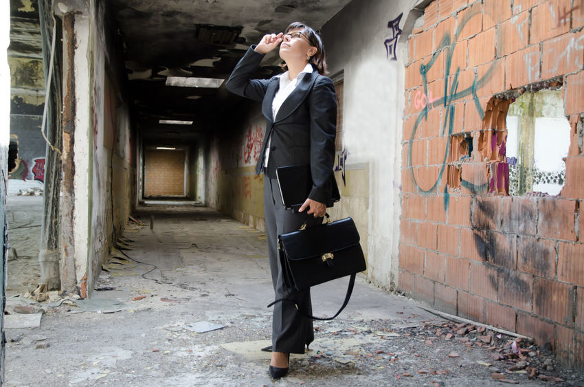 Architect woman controlling an old building Adult Adults Only Architecture Bag Building Business Business Business Woman Controlling Day Elégance Eyewear Indoors  Inside Of Looking Up Old One Person One Woman Only People Tunnel Wall - Building Feature Well-dressed Woman Working Young Adult