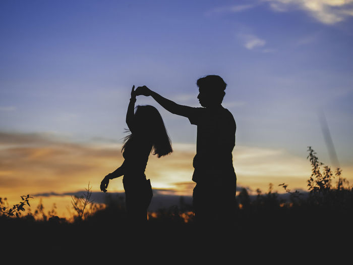 Silhouette couple standing on land against sky during sunset