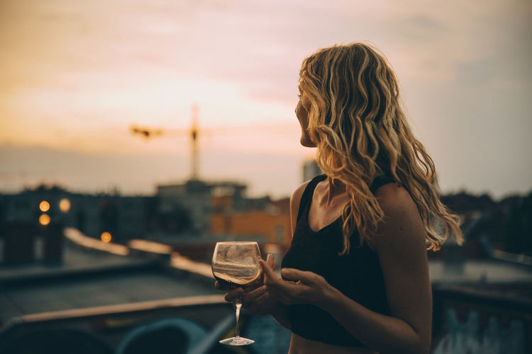 Midsection of woman drinking glass against sky during sunset