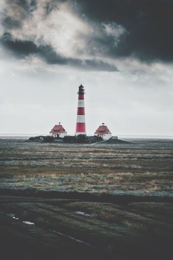 Lighthouse on grassy field against cloudy sky