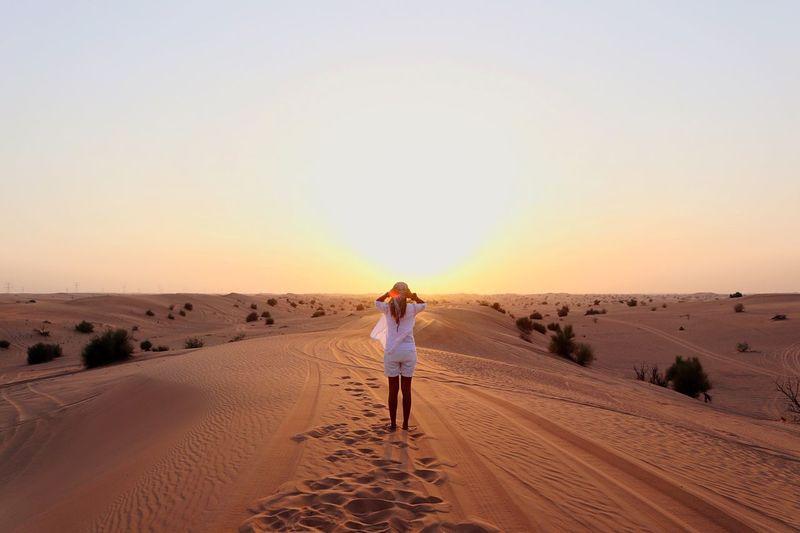Full length portrait of man standing on sand dune in desert