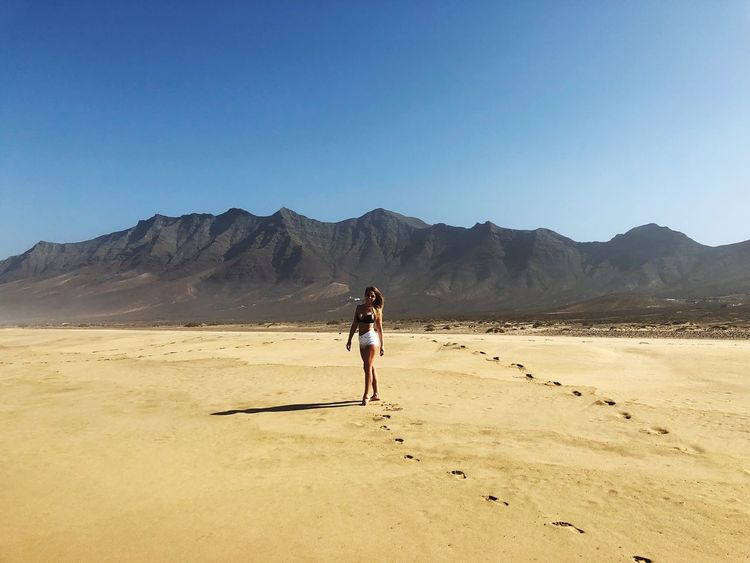 Full Length One Person Desert Clear Sky Sand Real People Blue Arid Climate Day Outdoors Sunlight Nature Lifestyles Landscape Mountain Sky Beauty In Nature Young Adult Sand Dune Adult Ocean Sun Photo Photography