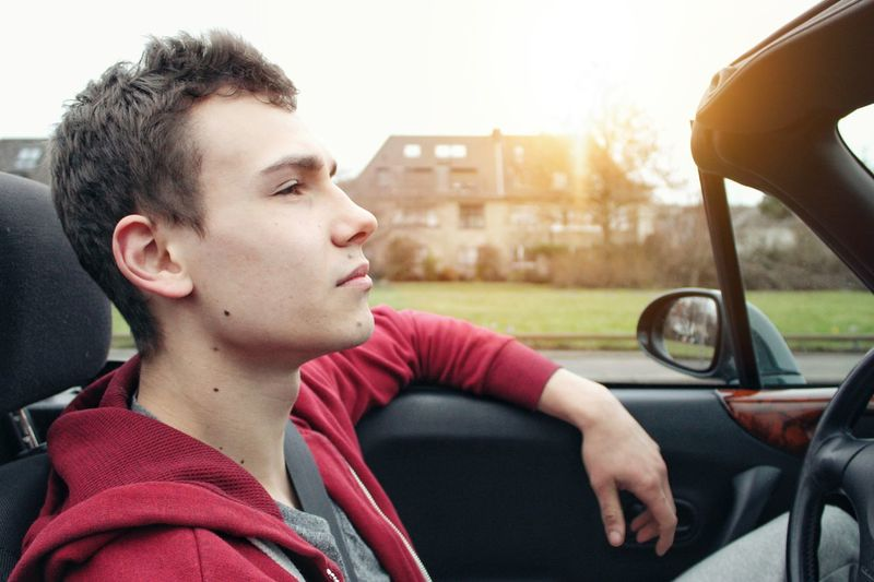 Close-up of young man sitting in car