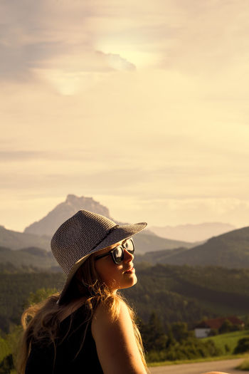Beautiful woman wearing sunglasses and hat during sunset