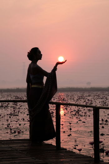 Optical illusion of woman holding sun while standing by lake against sky during sunset