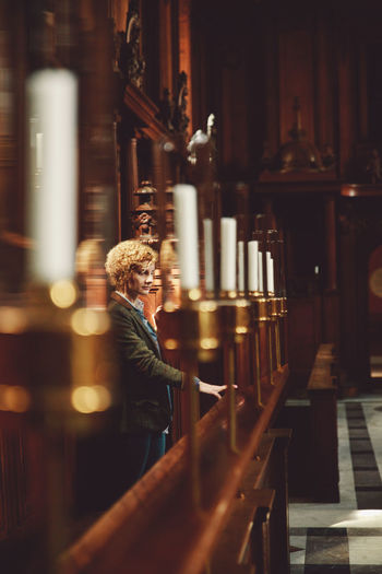 Thoughtful woman standing at pew in church