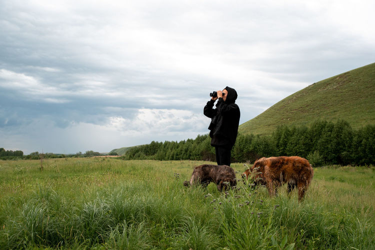 Man with horse standing on grass