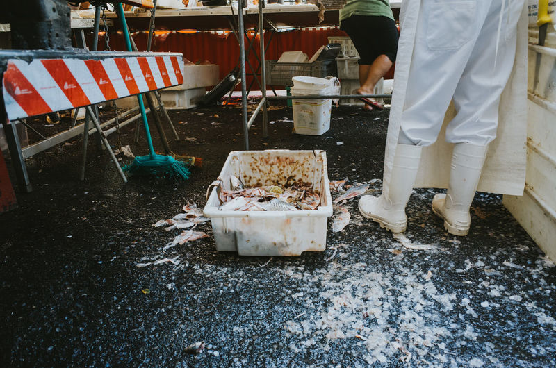Low section of man working at market stall surrounded by fish scraps