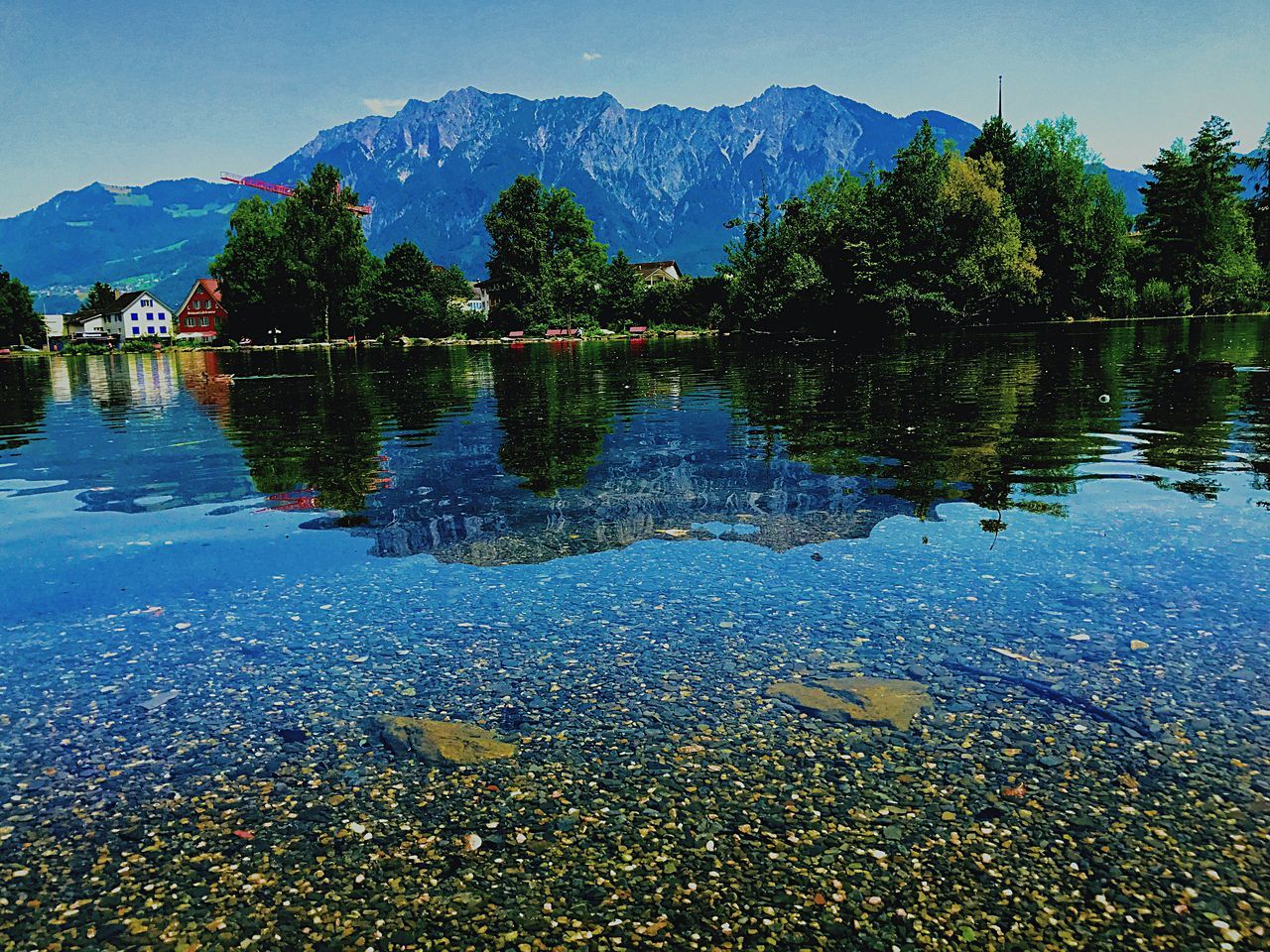 reflection, water, lake, mountain, tree, nature, scenics, tranquil scene, beauty in nature, tranquility, outdoors, no people, day, sky, mountain range, waterfront, blue, clear sky, animal themes