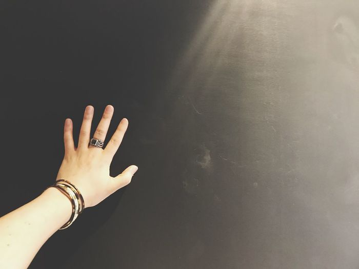 Cropped hand of woman wearing bangles and ring by sunlight in darkroom
