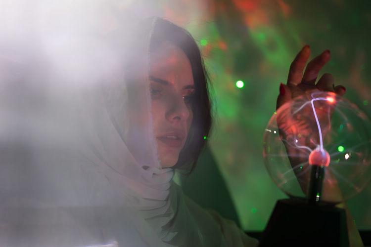 Portrait of woman holding illuminated glass