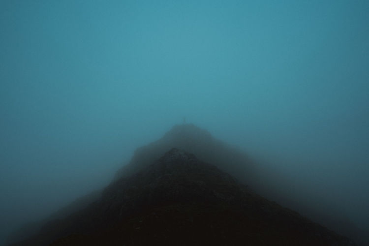 Silhouette mountain against sky during foggy weather