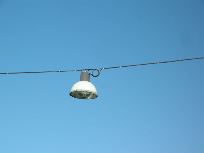 Electric Lamp Hanging On Cable Against Blue Sky