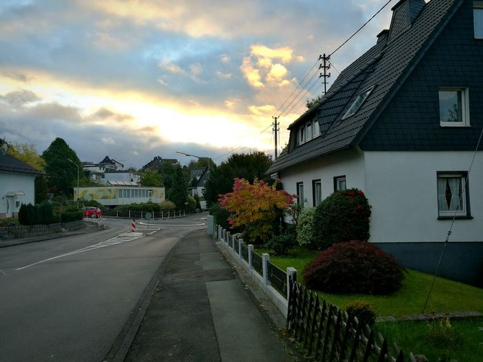 Road amidst trees and houses against sky during sunset