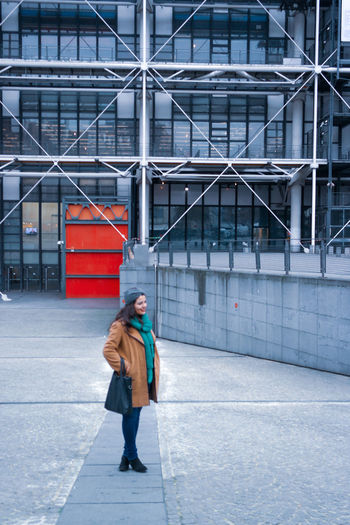 Full length side view of woman walking against pompidou centre  in paris