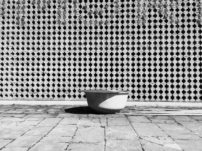 Container by patterned wall on sunny day