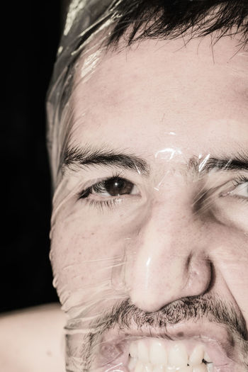 Close-up portrait of man covered in plastic against black background