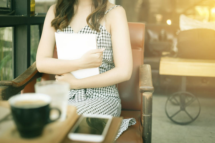 Midsection of woman sitting on table at cafe