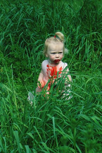 High angle view of girl with blood standing on grassy field