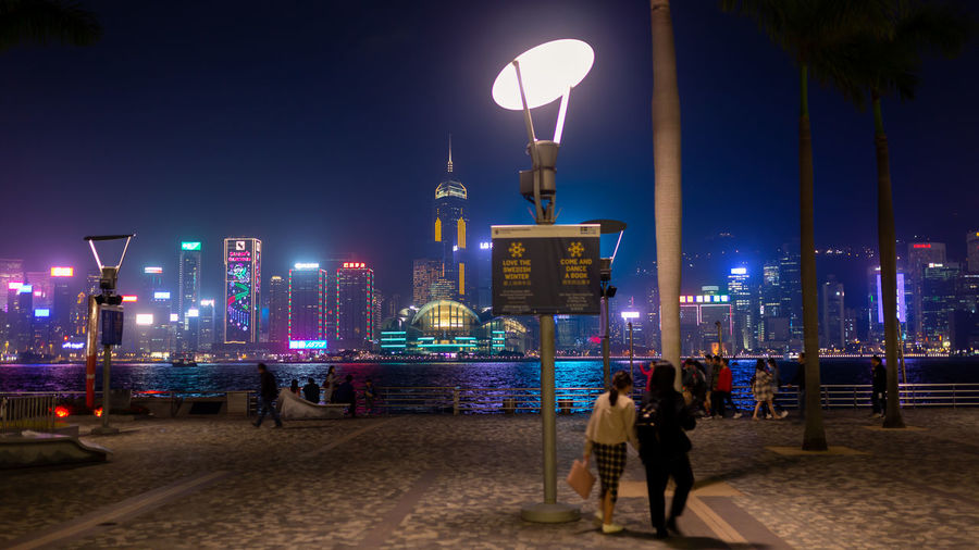 People on footpath against sea and illuminated buildings in city at night