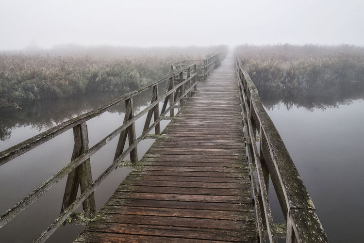 Wooden footbridge over lake against sky