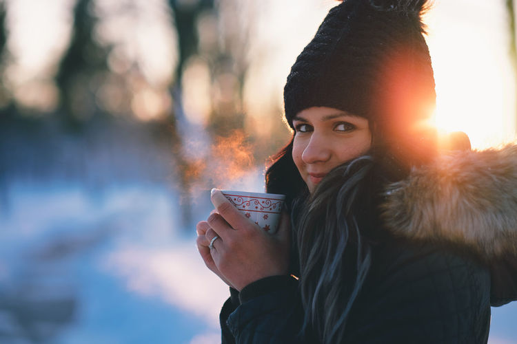 Side View Portrait Of Woman Wearing Warm Clothing Holding Hot Drink In Winter