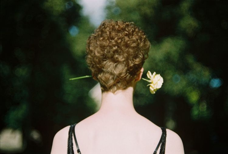 Rear View Of Woman With Flower At Park