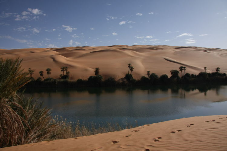 Scenic view of desert against sky with sahara lake oaisis