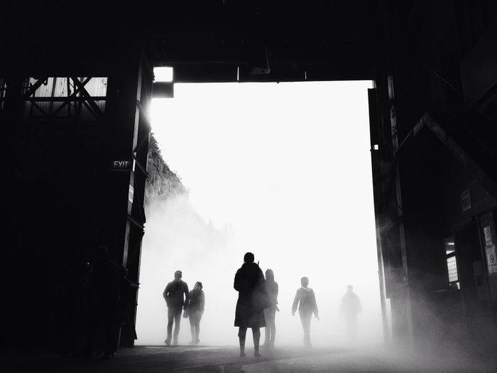 Silhouette Of People Entering And Leaving Building
