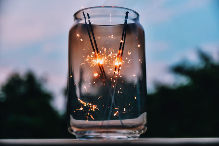 Close-up of sparklers burning in jar on table against sky