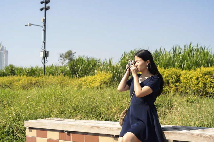 Young woman holding camera on field against clear sky