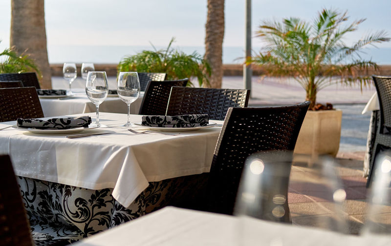 Empty outdoors restaurant. Table setting with a wine glasses, cutlery and plates Outdoors Restaurant Palm Tree SPAIN Summertime Table Setting Table Arrangements Tableware Wine Glass Crockery Drink Drinking Glass Empty Restaurant Food And Drink Glass Glassware No People Outdoors Place Setting Restaurant Setting Summer Table Table Appointments Tablecloth Wineglass