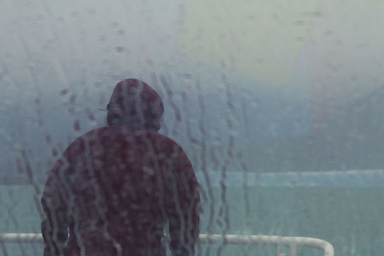 One Person Rear View Men Real People Lifestyles Waist Up Day Portrait Water Headshot Adult Leisure Activity Standing Nature Mystery Wall - Building Feature Contemplation Rain Rainy Days Outside