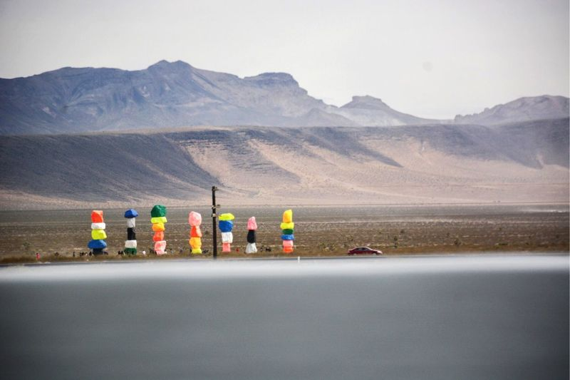 Stack of colorful rocks on roadside against mountains