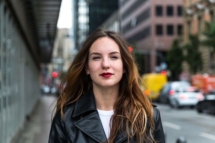 Portrait of young woman wearing a trench coat in city One Person Looking At Camera Beautiful Woman Trench Coat Fashion Beauty Lipstick Attractive Woman Urban Caucasian Young Adult Outdoors Day Autumn Brunette Portrait Young Women Focus On Foreground Headshot Front View