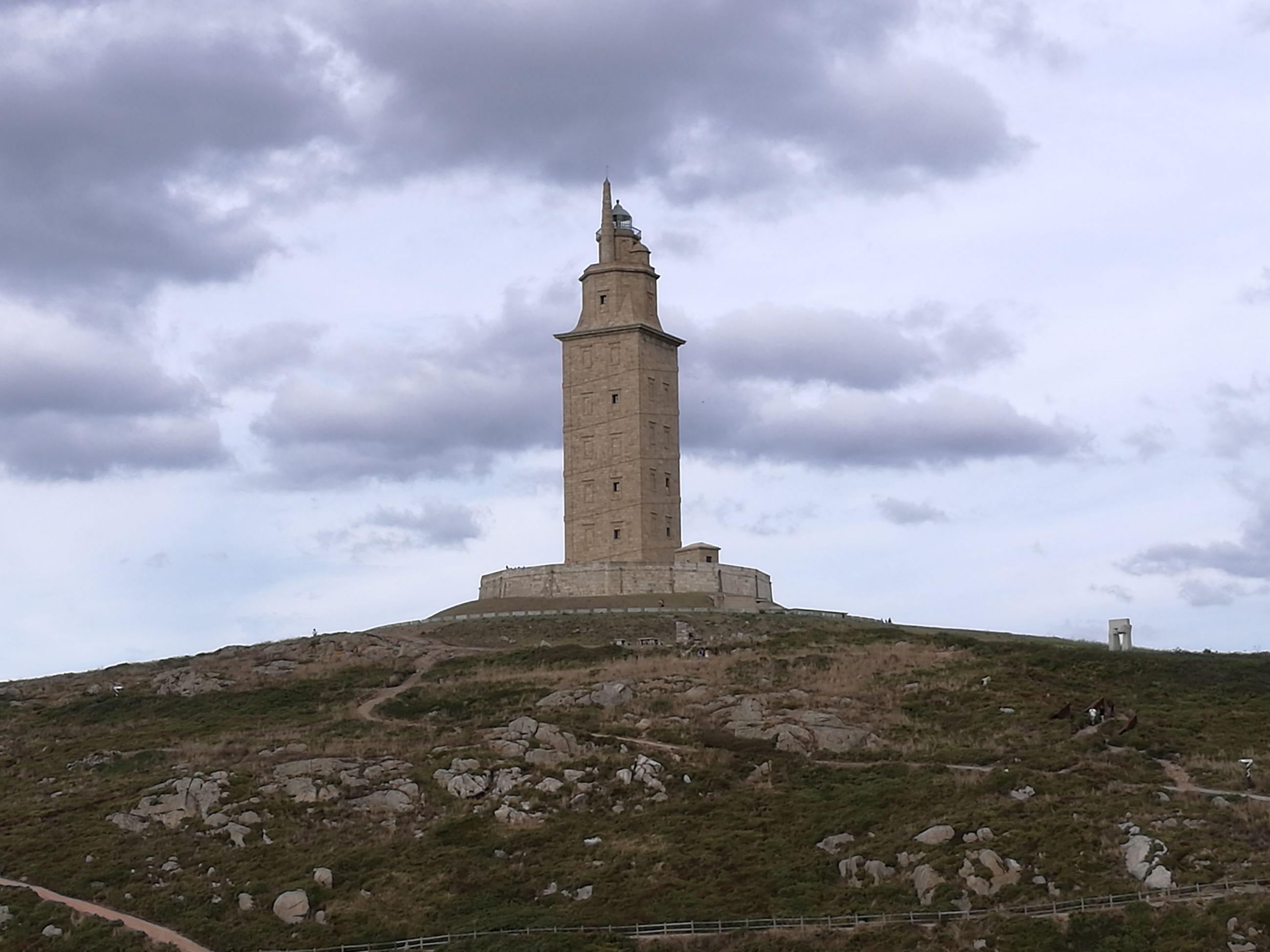 architecture, built structure, protection, lighthouse, direction, guidance, tower, cloud - sky, safety, building exterior, sky, history, the past, cloudy, cloud, travel destinations, outdoors, tranquility, tourism, tall, tall - high, stone material, tranquil scene, nature, scenics, architectural column, non-urban scene, no people, storm cloud