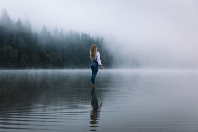 Full length of man in lake during foggy weather