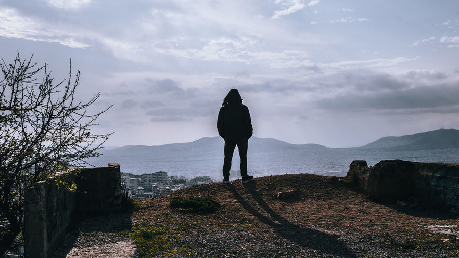 Rear view of woman standing on landscape against sky