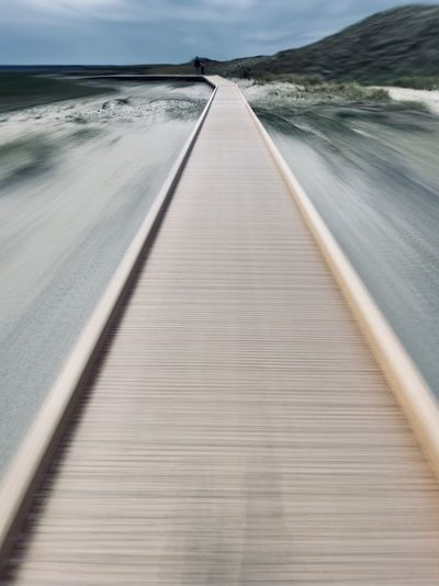 Surface level of pier on sea against sky