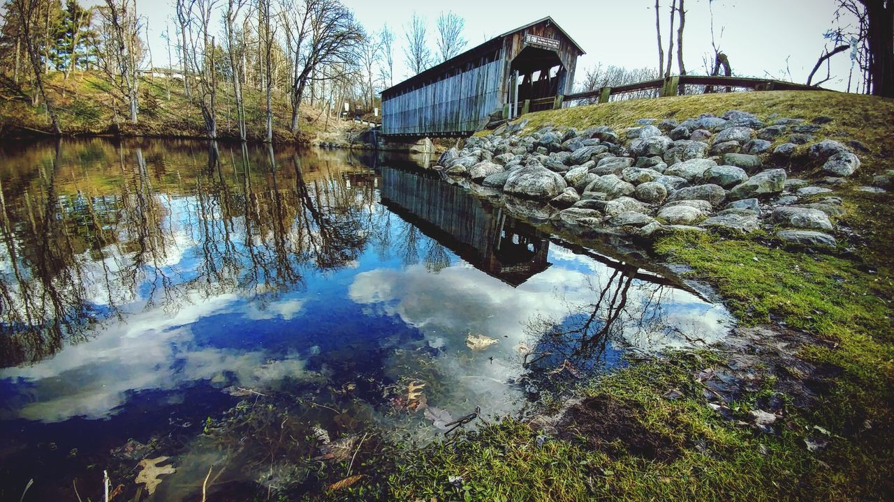built structure, architecture, water, reflection, day, nature, building exterior, tranquility, lake, no people, outdoors, rock - object, watermill, tranquil scene, beauty in nature, tree, sky, scenics