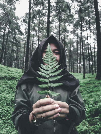 Close-up of young woman holding plant against her face in forest