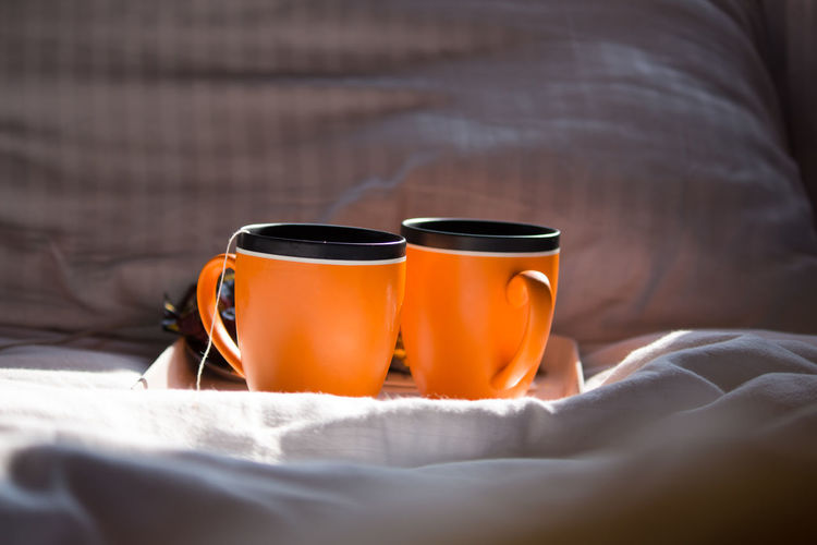Close-up of tea cup on bed