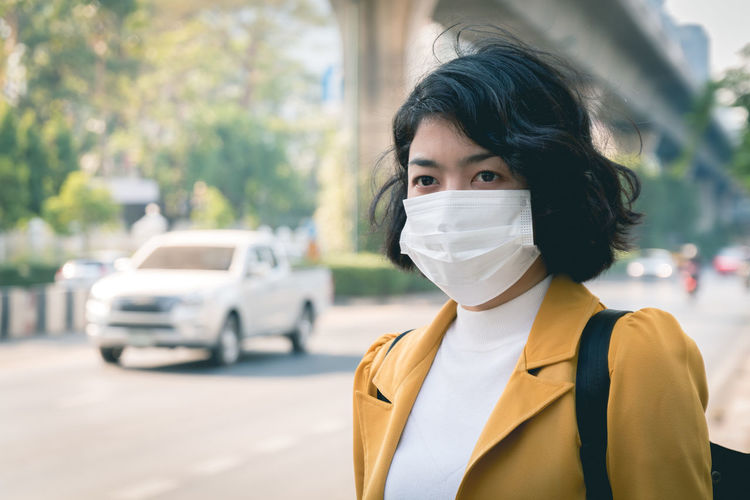 Close-up of woman wearing mask looking away while standing outdoors