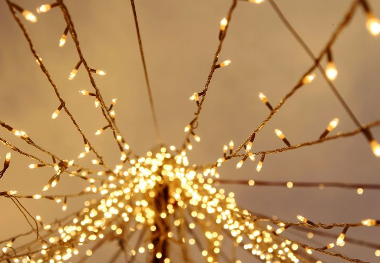 Illuminated christmas lights against ceiling