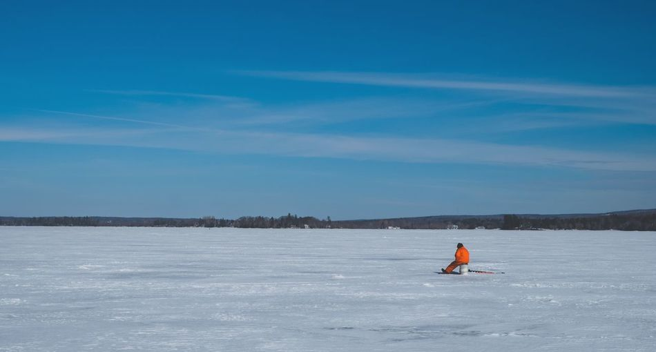 Person Sitting On Pole Over Frozen Lake Against Sky