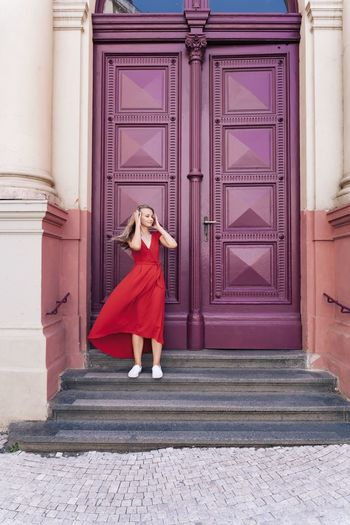 Full length of woman standing on steps against closed doors