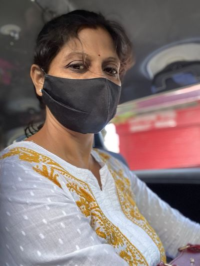Portrait of woman wearing mask driving car