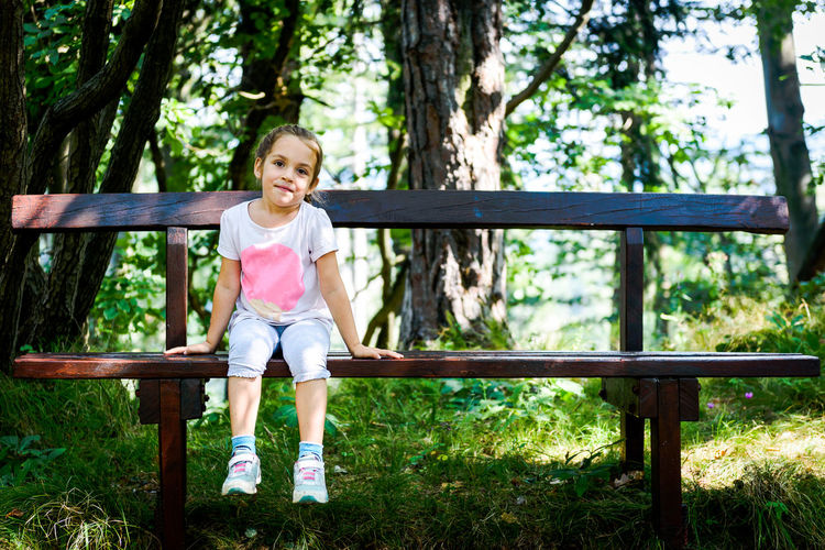 Portrait of smiling girl sitting on bench in forest
